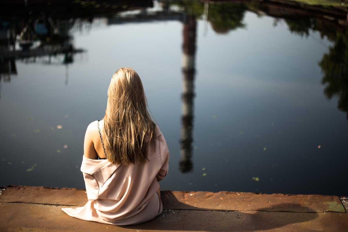 Mulher sentada ao lado de lago