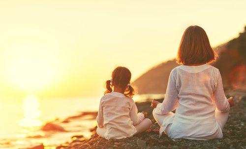Mãe e filha praticando ioga