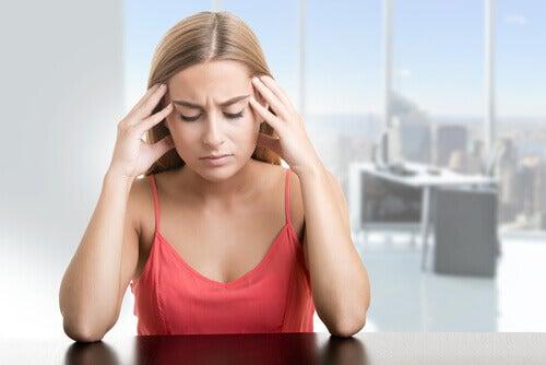 Mulher sentindo cansaço e dor de cabeça