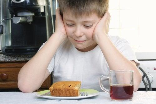 Menino com síndrome da alimentação seletiva que não quer comer a comida do prato