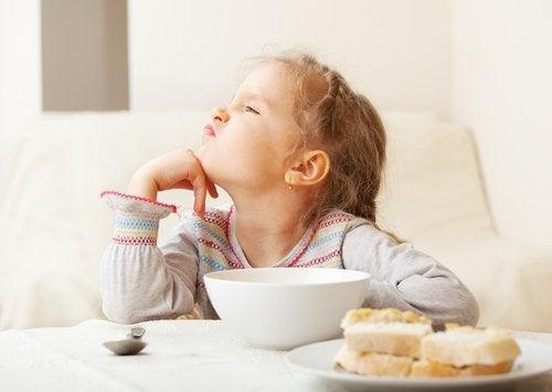 Menina com síndrome da alimentação seletiva que não quer o café da manhã