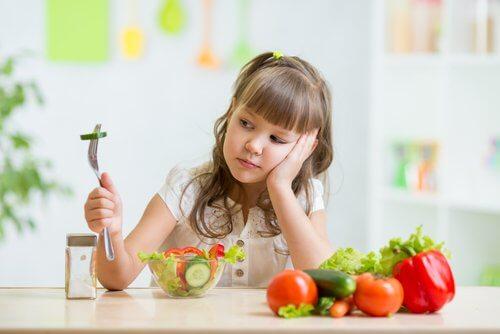Menina com síndrome da alimentação seletiva que não gosta de vegetais