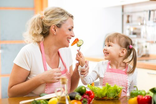 Mãe ensinando sua filha a se alimentar bem