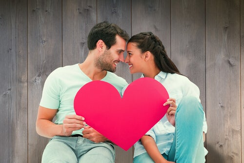 Casal segurando coração vermelho