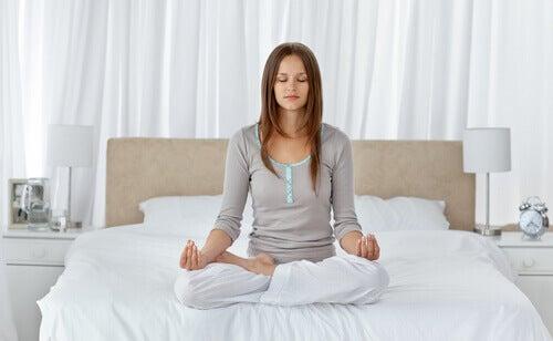 Mulher meditando na cama