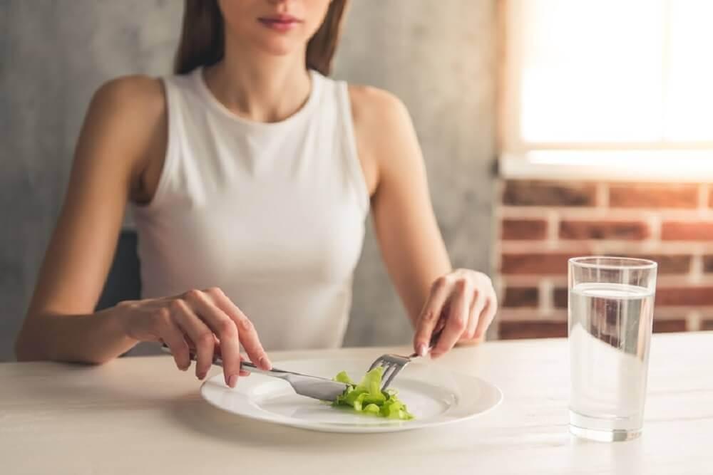 Mulher comendo folha de alface