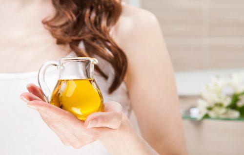 Mulher segurando jarra de azeite