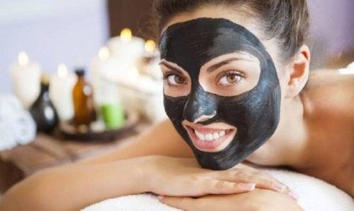 Mulher com máscara negra no rosto para eliminar os cravos e impurezas