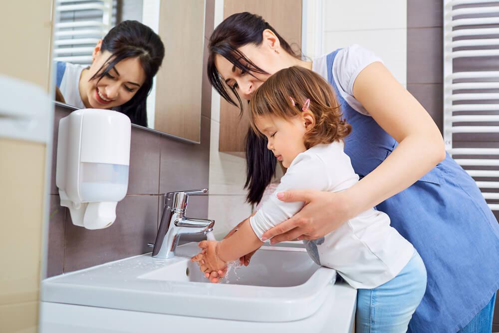 Mãe ensinando filha a lavar as mãos