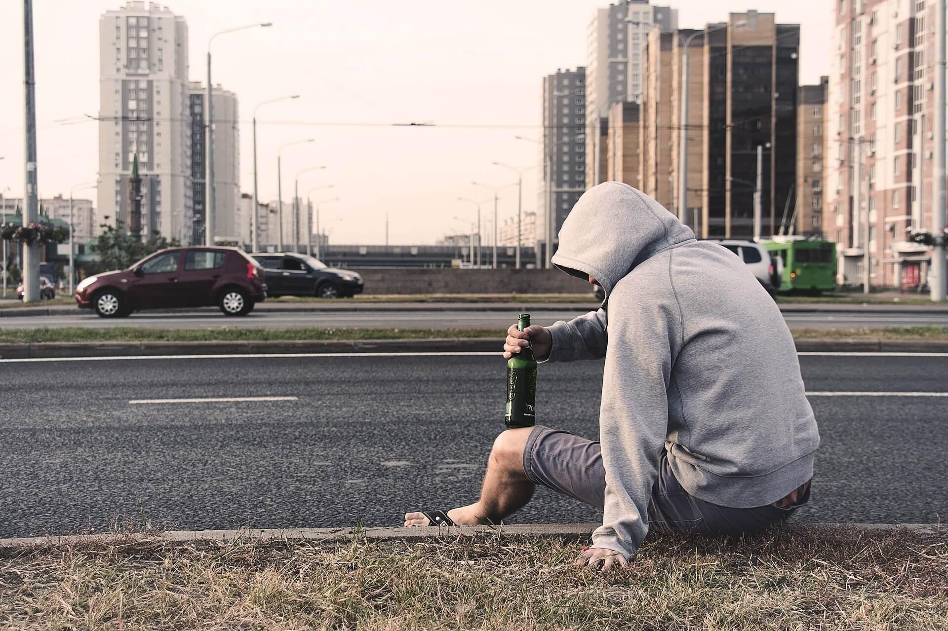Homem com garrafa bebendo álcool no meio-fio