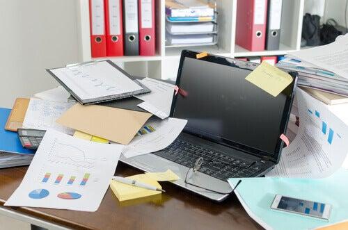 Laptop sobre mesa de trabalho bagunçada