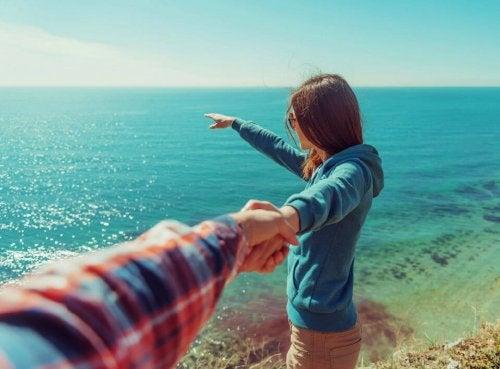 Mulher olhando para o mar segurando da mão de um homem