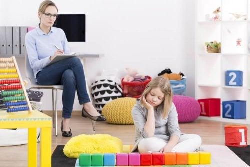 Menina com síndrome de Asperger sentada brincando
