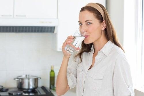 Mulher bebendo água em sua cozinha
