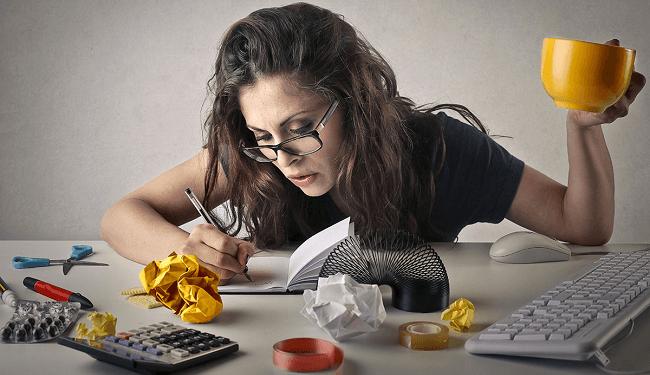Mulher escrevendo, trabalhando, tomando café, estressada