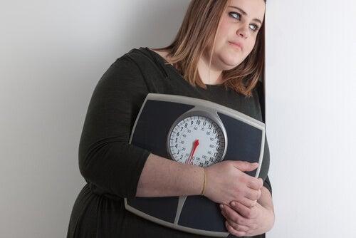 Mulher com sobrepeso segurando uma balança