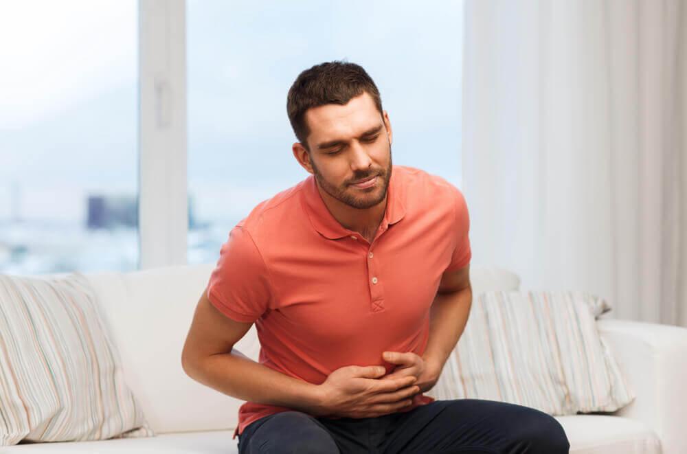 Homem sentindo estômago pesado