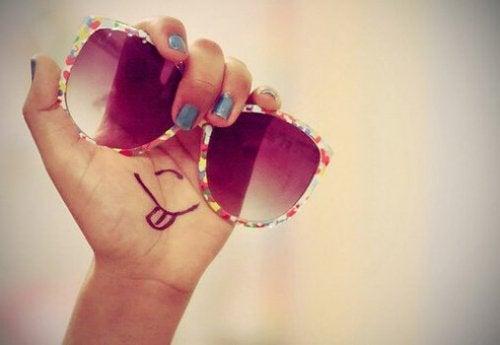 Mão segurando óculos colorido