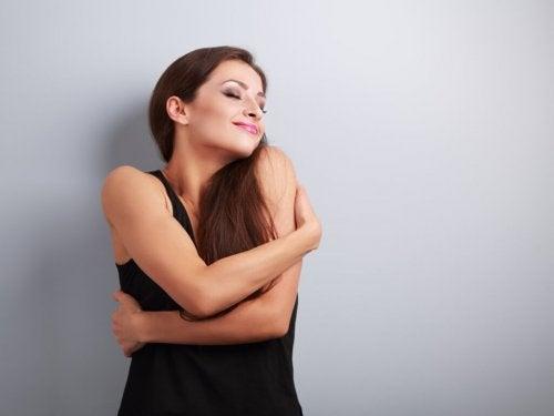 Mulher que ama a si mesma se abraçando