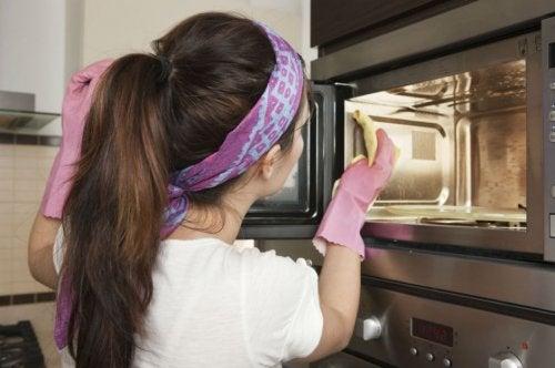 Mulher limpando micro-ondas