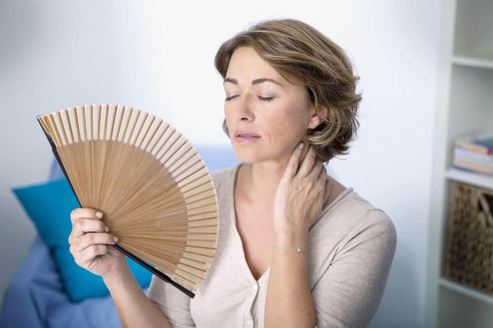 Mulher sentindo calores da menopausa