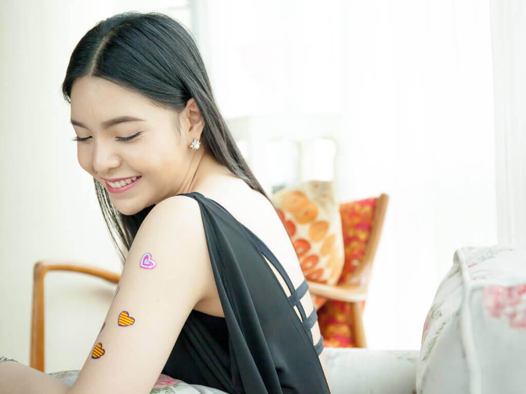Moça com tatoos no braço