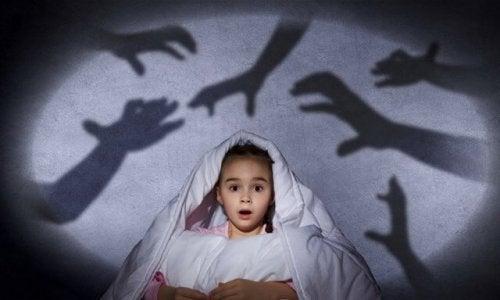 Criança com medo das sombras no escuro