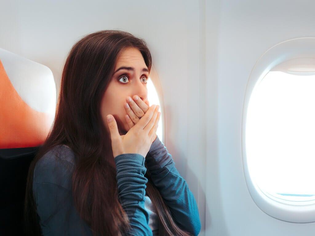 Mulher com vontades de vomitar no avião