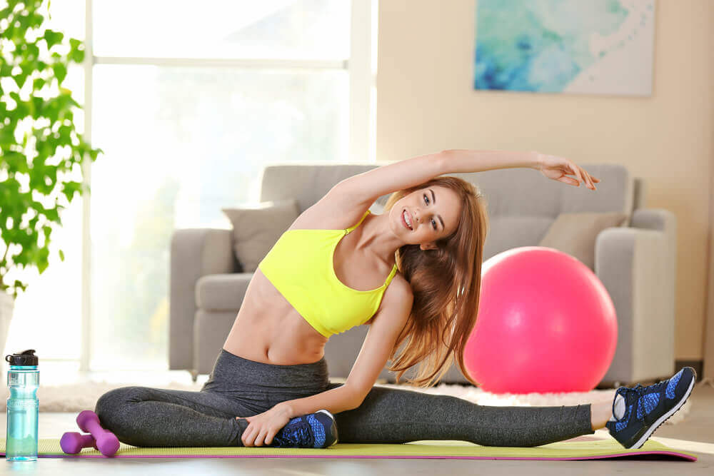 Mulher fazendo alongamento com bola de pilates