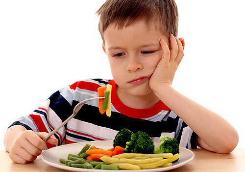 Criança brincando com os vegetais para não comê-los