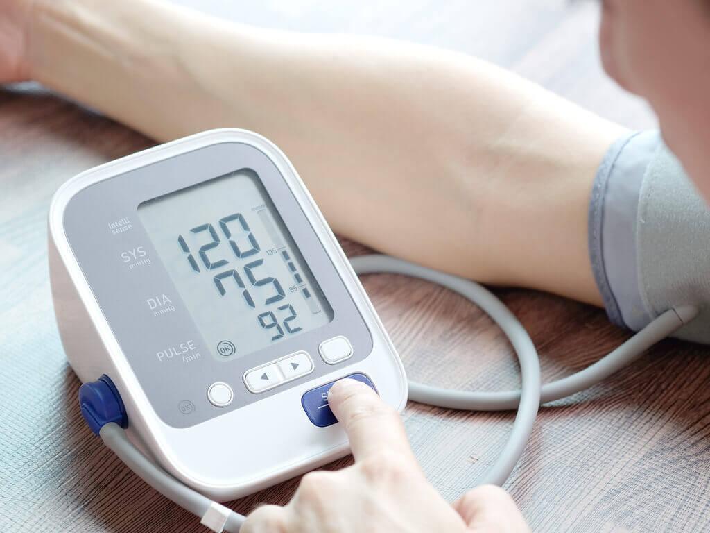 Pessoa tirando a pressão arterial em casa