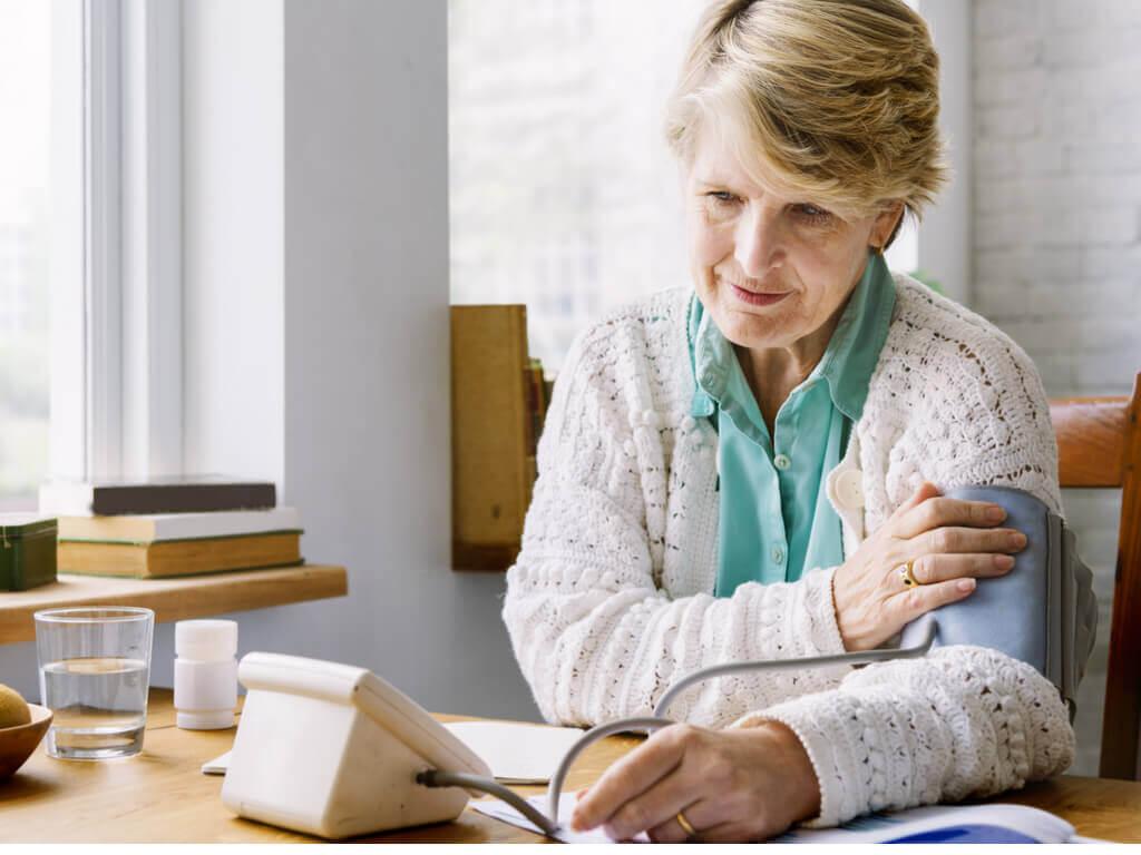 Mulher tirando sua pressão arterial em casa