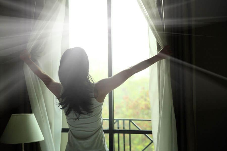 Mulher deixando a luz natural entrar no quarto