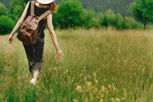 Mulher caminhando no campo, na natureza