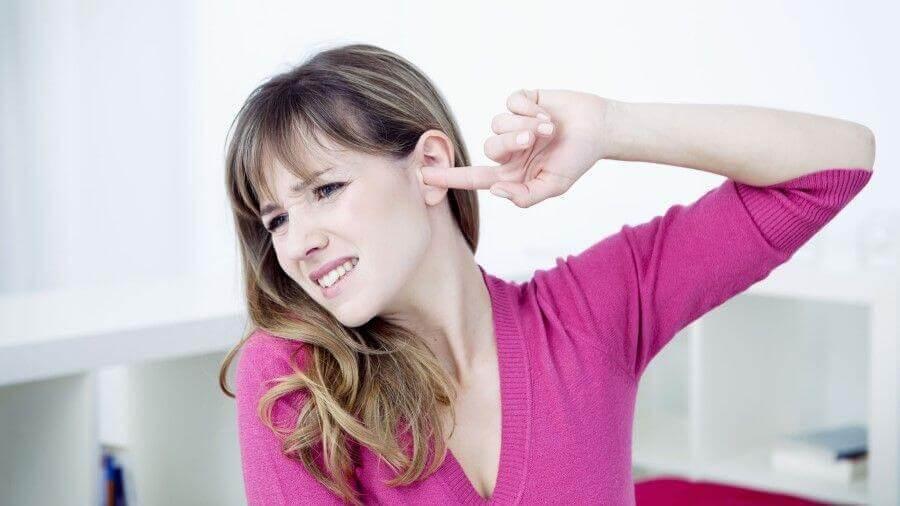 Mulher com dedo no ouvido: zumbido