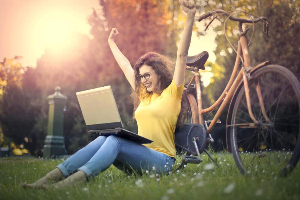 Mulher feliz diante de seu notebook