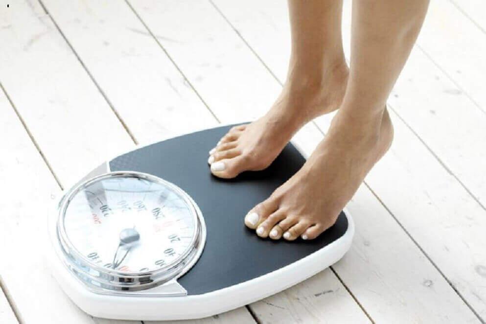 Mulher se pesando na balança