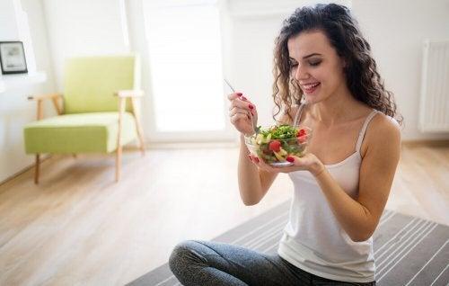 Mulher comendo uma salada em casa