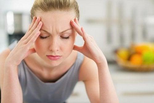 Mulher com dor de cabeça por causa do refluxo gastroesofágico