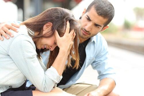 Mulher chorando e homem apoiando-a ao seu lado