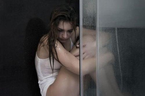Mulher triste sentada no chuveiro