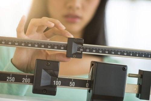 Mulher se pesando em balança