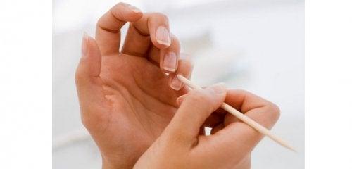 Mulher usando óleo de coco nas unhas