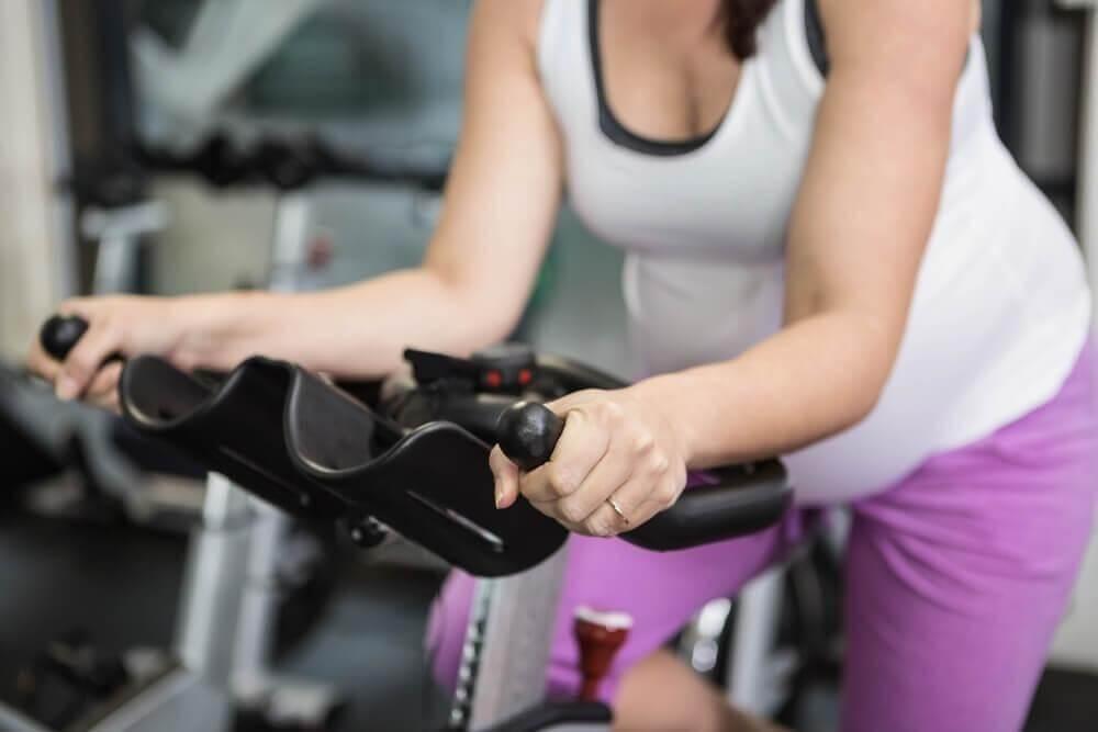 Mulher fazendo bicicleta na academia