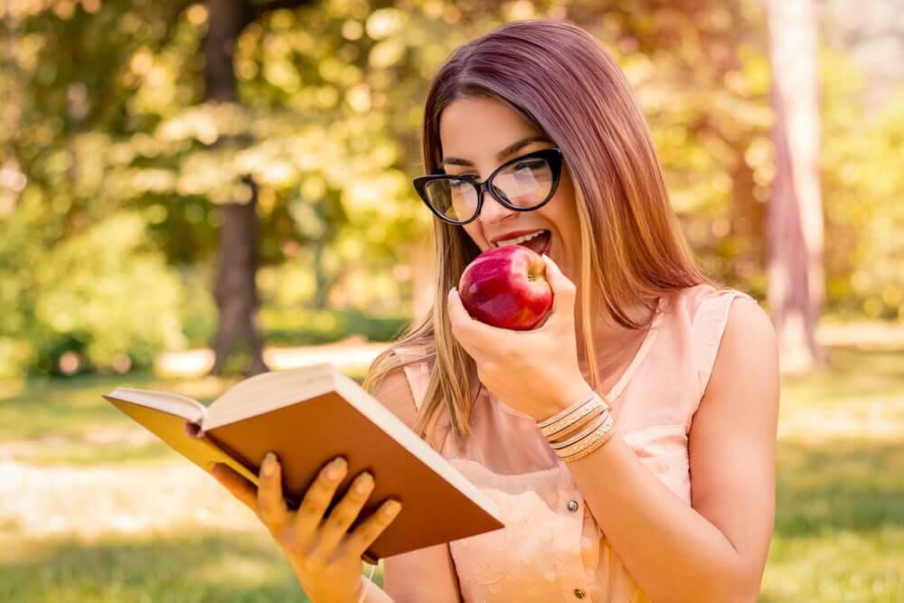 Mulher lendo livro e comendo maçã