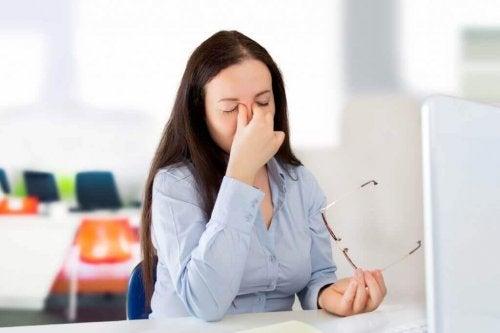 Mulher com visão embaçada no trabalho