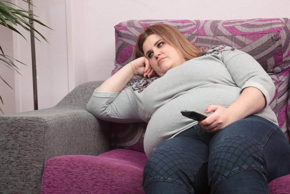 Mulher obesa sentada no sofá