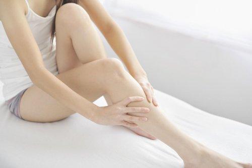Mulher fazendo massagem para aliviar a dor nas pernas