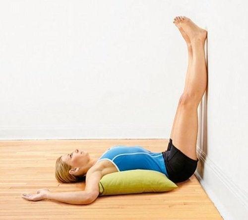 Mulher com as pernas para o alto para aliviar a dor nas pernas