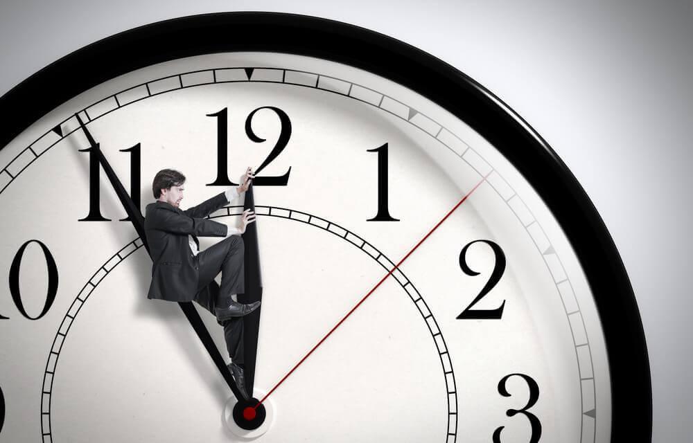 Homem segurando o ponteiro do relógio